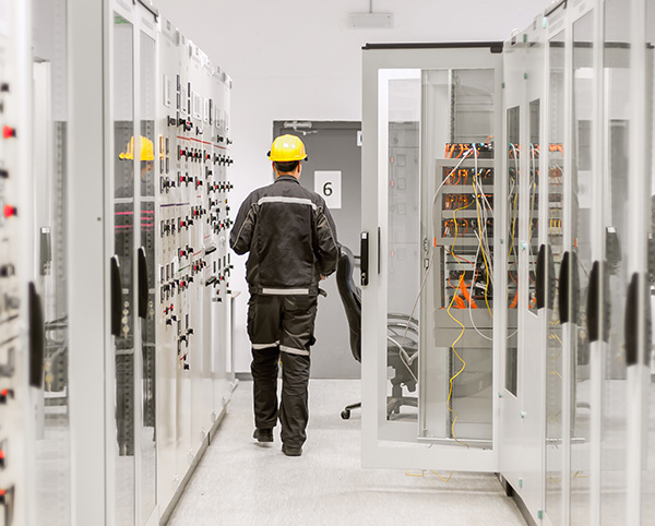 A worker does a walk through in a mission critical systems facility